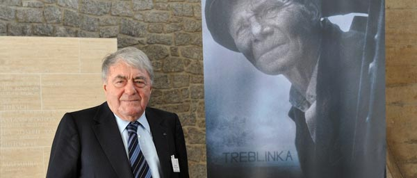 Director Claude Lanzmann with a poster for the film Shoah. A Claims Conference grant allowed the film to be shown and distributed in 10 Muslim countries.