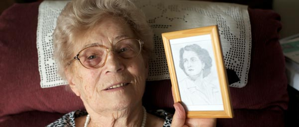 Agnes holds a drawing of Edith Kiss, who saved Agnes' life by helping her escape Ravensbruck. Agnes has many paintings and drawings made by Edith, an artist, after the war.